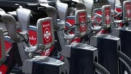 A row of bicycles available to hire stand in the street with logos of sponsor Banco Santander SA in London UK on Tuesday Aug 15 2017