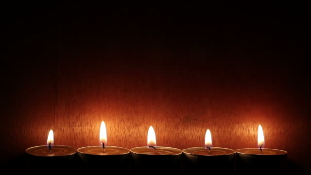 Row of candles with wooden walls in dark room.