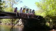 MS, row of children (8-11) sitting on wooden bridge, Bovina, New York State, USA