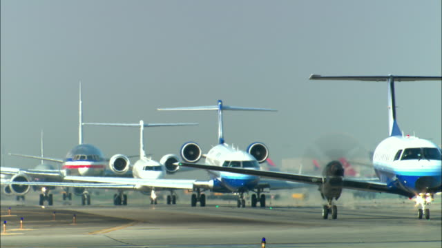 MS, Row of commercial jets taxiing on runway, Los Angeles, California, USA
