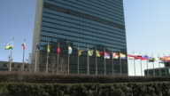 Row of flags flapping in wind in front of United Nations building/ New York City New York USA