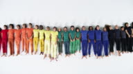 Row of People Lying Down on White Studio Floor, Zoomed Out
