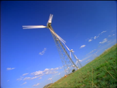 CANTED row of spinning wind turbines on plain