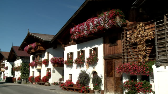 Row of traditional houses with flower boxes in full bloom and traditional harvest cross  m