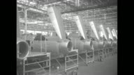 LS row of wing assemblies on factory floor as F84 jets are assembled for use by the US Air Force workers work with wings / montage driveby shots of...