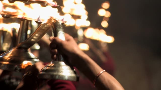 CU, SELECTIVE FOCUS, Row of young men performing Aarti ritual at night, Varanasi, Uttar Pradesh, India