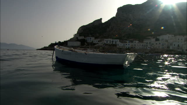 A rowing boat is anchored off the coast of a small Mediterranean town. Available in HD.