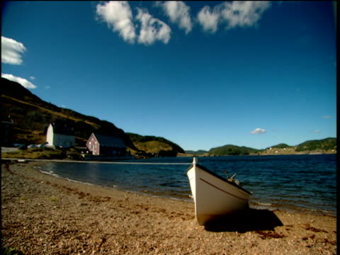 Rowing boat on shore with few houses near Atlantic sea bay