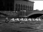 Rowing coach w/ megaphone WS Boat w/ rowers seated coxswain moving on river under bridge arch Iconic tradition Ivy League athletics