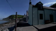 Rows of cottages line the rocky shores of Crovie, Scotland. Available in HD.