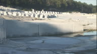 Rows of granite blocks are staged at the base of a hill near a quarry.