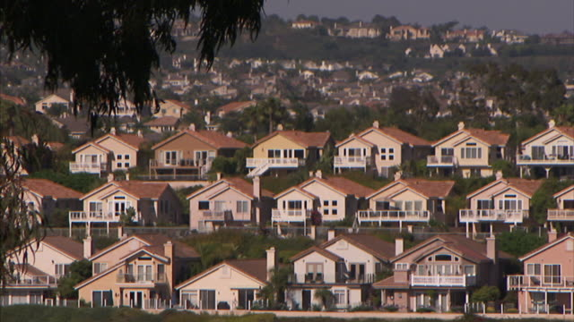 Rows of identical two-story houses cover a hillside in a Los Angeles suburb.