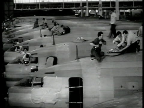 Rows of incomplete airplanes workers on top MS Workers on top examining airplanes Two men testing landing gear lowering wheel Men moving motor on...