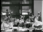 B/W 1927 rows of men + women working at desks / one man on dictaphone / industrial