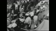 rows of pushcarts and street vendors possibly near Hester Street which at the turn of the century was the center of commerce for New York's Jewish...
