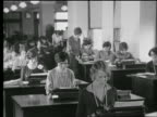 B/W 1927 rows of women sitting at desks in office typing / industrial