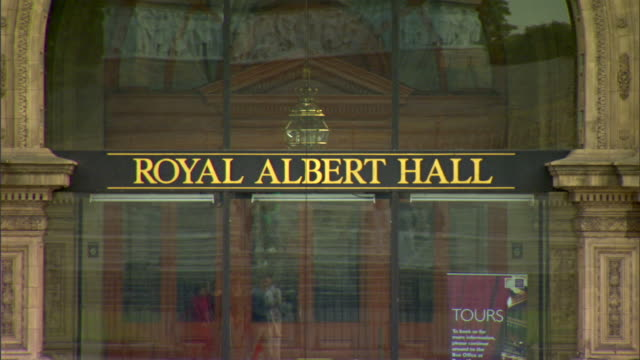 Royal Albert Hall sign above doorway traffic red bus passing through frame reflection of people walking in building glass