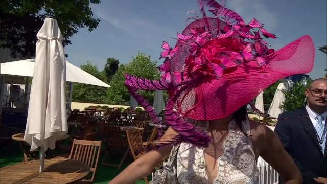 Royal Ascot considers relaxing dress code ENGLAND Berkshire Ascot EXT Butterfly decoration on hat PULL OUT Woman along with green feathered hat Lady...