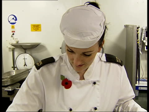 HMS Illustrious Kitchen staff including female chef wearing white cook's overalls and poppy buttering oven dishes and lining them with sheets of...