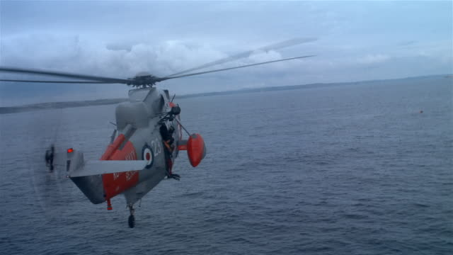 AIR TO AIR, Royal navy rescue helicopter flying above plane crashed in sea, France