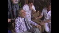 Celebrating supporters man shakes and sprays champagne / Prime Minister Bob Hawke into crowded celebrating room sprayed with champagne laughs and...