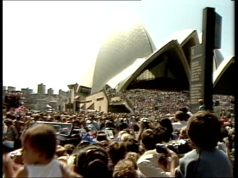 Week 2 28383 Sydney SEQUENCE Large crowds in front of Opera House city school band playing Airviews high school dancers Charles and Diana looking...