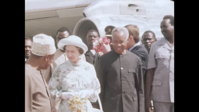 Dar es Salaam MS Queen Elizabeth II Prince Philip and Prince Andrew off plane and greet Julius Nyerere MS Receive bouquet and garlands MS Philip...