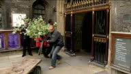 Flowers arriving at Westminster Abbey cloisters INT Trolleys of flowers wheeled through gates More of flowers being unloaded from back of lorry INT...