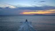 Luchtfoto rubberboot dobbert rijden op zee bij zonsondergang