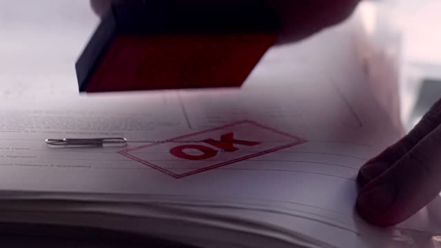 Rubber stamping a paper document with OK    OK