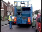 Rubbish collectors attach green wheelie bins to back of rubbish truck which automatically empties them