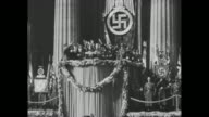 Rudolf Hess standing on platform with group of Nazi officials administering oath they raise hands in Nazi salute large Swastika on stand behind them...