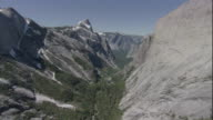 Rugged rock peaks tower over a valley in Yosemite National Park. Available in HD.