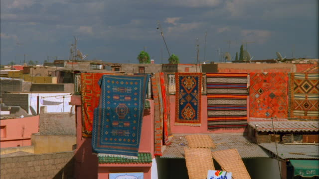 Rugs hanging on washing line on roof of apartment building Available in HD.