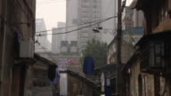 MS ZO WS Run down houses with high rise apartment building in background / Nanjing, China