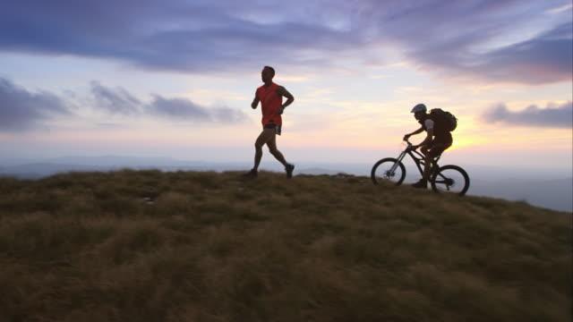 TS runner en mountainbiker op het plateau bij zonsondergang