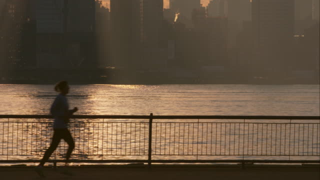 A runner in silhouette with the Manhattan Skyline behind