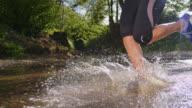 SLO-MO-LA-Läufer läuft über einen kleinen Bach im Wald