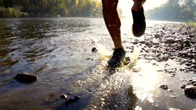 HD SUPER SLOW-MO: Runner Splashing In The River