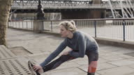 Runner stretches legs and arms and starts jogging.