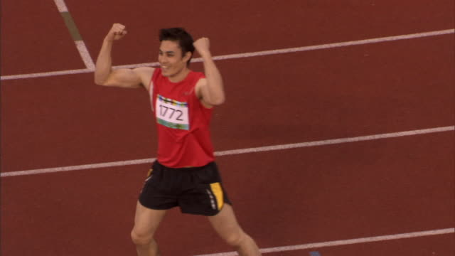 HA MS ZI Runner winning race, waving, and making victory gestures to crowd/ Sheffield, England