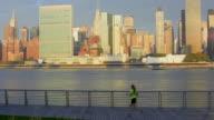 Runner with Midtown Manhattan in background at sunrise