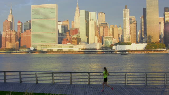 Runner with Midtown Manhattan in background at sunrise