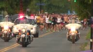 Runners in road race Start of race to camera lead vehicles in shot