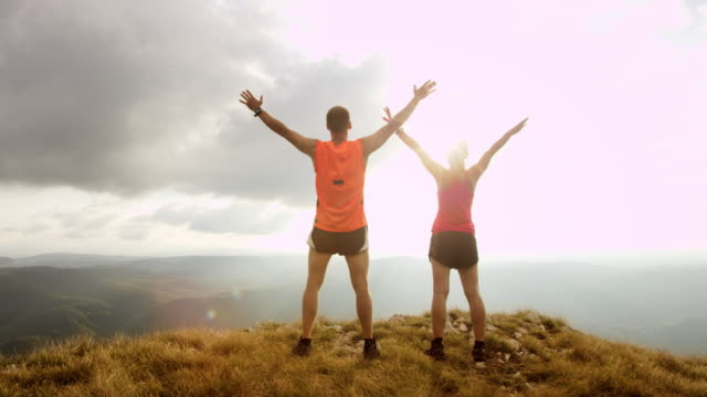 TS SLO MO runners raising hands on mountain top