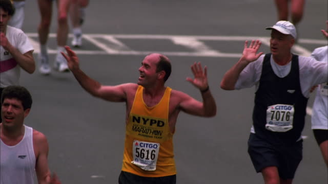 Runners wave to crowds while heading for finishing line at Boston Marathon, Massachusetts Available in HD.