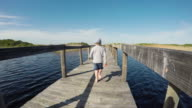 POV running behind a young boy on the wooden bridge