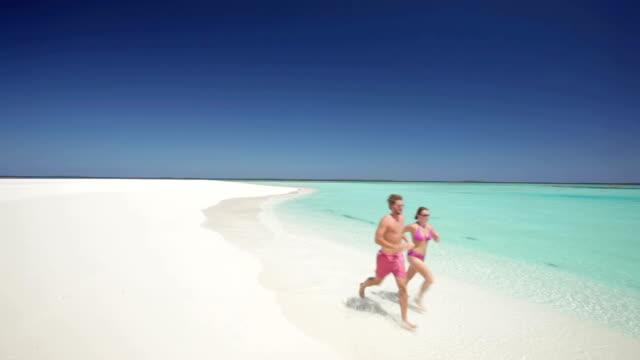running couple on sandy beach