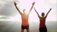 TS SLO MO runnen paar bereiken van de top bij zonsondergang