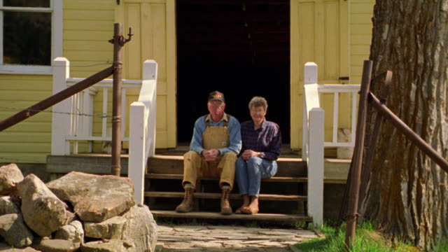 PORTRAIT rural senior couple sitting on steps of porch + waving to camera / Montana